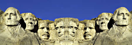 This is a digitally created image. It is a double image of Mount Rushmore connected at its center against a blue sky.