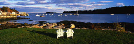 This is an image of two white lawn chairs facing toward the nearby harbor.  photo