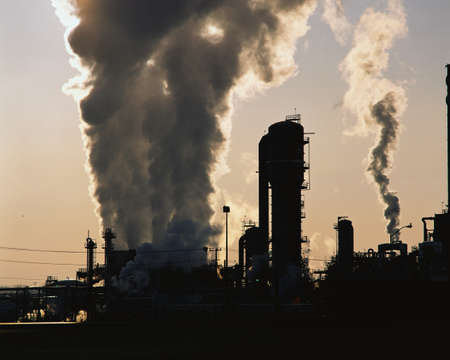 polluting: This is an image of an industrial plant pushing billowing stacks of smoke into the sky.