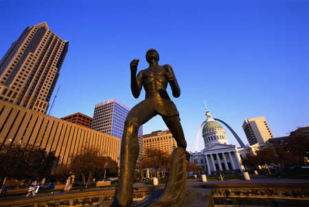 This is the Old Courthouse with a close up of the statue in front of the courthouse and State Capitol. In the background is the skyline and arch.