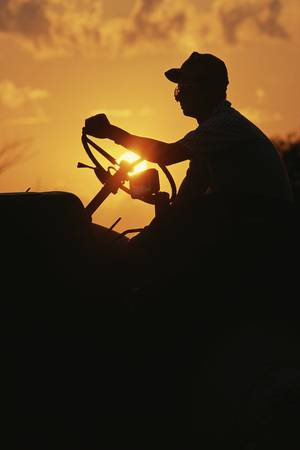 Farmer silhouetted by early morning sun