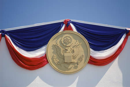 Red, white, and blue drapery with presidential seal photo
