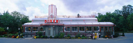 This is the Eveready Diner. It is a 50's style diner whose building looks similar to an old train car. The roof is made from a silver chrome with windows all across the front. There is a red neon sign that says Diner.  新闻类图片