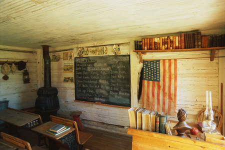 country life: This is the interior of a one room school house. It was the first school in Montana from 1868. There is a black chalkboard and American flag hanging on the wall with a black wood furnace stove in the corner. There are a couple of old fashioned school desk Editorial