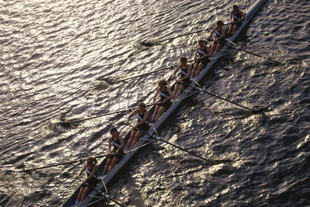 Crew team rowing in water
