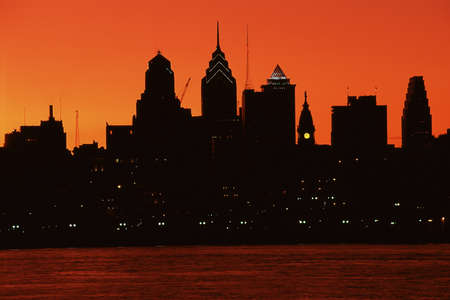Urban skyline silhouetted by sunset photo