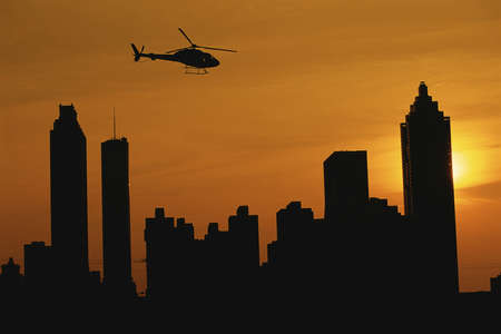 Helicopter flying over Atlanta skyline at sunset