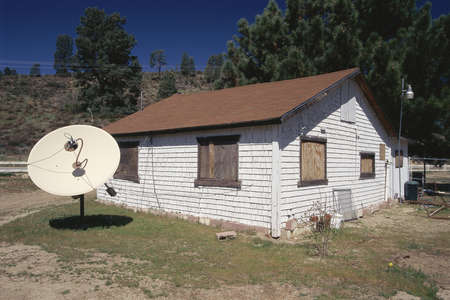 Cottage with satellite dish in yard