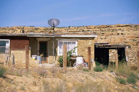 Mud-brick house with satellite dish Reklamní fotografie