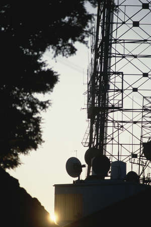Silhouetted antenna and relay dishes