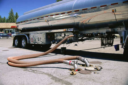 Gas truck filling underground tank Imagens