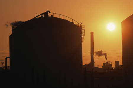 Oil refinery tank at sunset