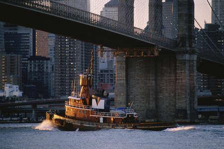 tug boat: Tug boat under Brooklyn Bridge, New York