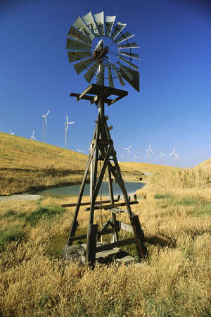 altamont pass: Old windmill with new windmills in background Stock Photo