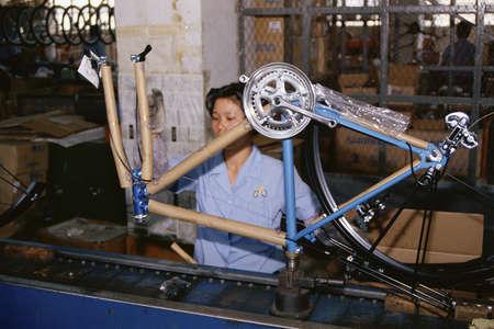 lopende band: Vrouw op fabricage assemblagelijn houdt fiets