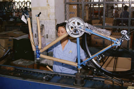 Woman on manufacturing assembly line holding bicycle