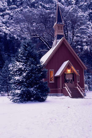 trees photography: Lit church against snowy surroundings