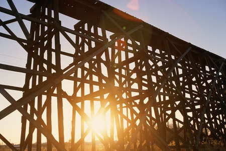 Red sunset shining through scaffolding of elevated train bridge