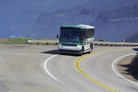 curve road: Bus rounding curve on road Stock Photo