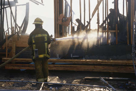 burned out: Firefighter hosing down building Stock Photo