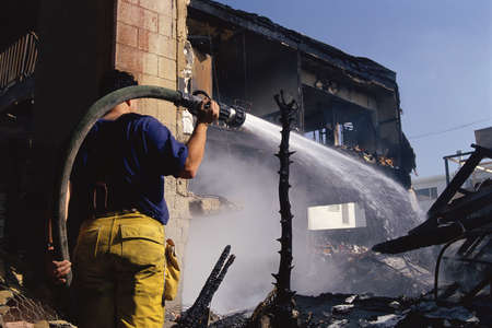 burned out: Firefighter aiming hose at charred building
