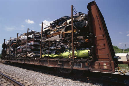 Junked smashed cars on railroad car