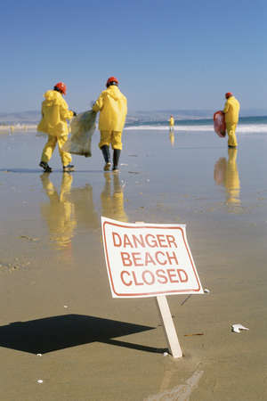cleanup: Clean-up crew on beach and warning signage