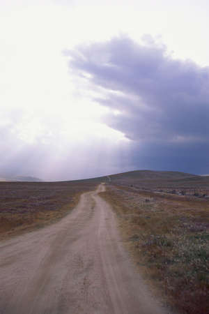 Isolated dirt road with dark clouds photo