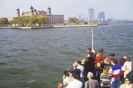 Tourists in boat viewing Ellis Island National Park, New York City, New York