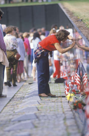 Woman Tracing Name of Soldier on the Vietnam Wall Memorial, Washington, D.C.