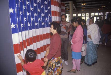 ellis: Ethnic family visiting an exhibit at Ellis Island National Park, New York