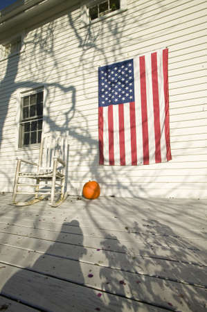 American flag, pumpkin and rocking chair on porch of home in Newport, Rhode Island