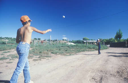 nm: Boys playing baseball on a desert road, San Miguel, NM