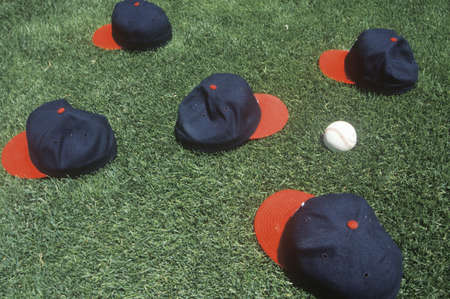Baseball caps and ball on field, Candlestick Park, San Francisco, CA 新聞圖片