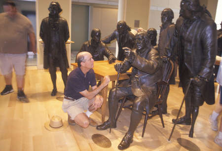 A tourist observing bronze replicas of the American founding fathers, National Constitution Center, Philadelphia, Pennsylvania