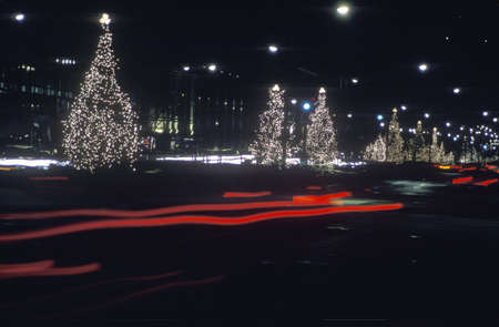 Lighted Christmas trees along roadside and automobile taillights at night, New York Stock Photo - 20514117