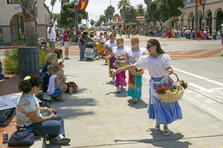 spaniards: Flower girls throwing flowers during opening day parade down State Street, Old Spanish Days Fiesta, August 3-7, 2005, Santa Barbara, California