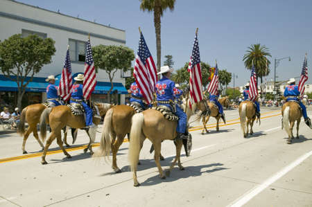spaniards: Cowboys marching with American Flags displayed during opening day parade down State Street, Santa Barbara, CA, Old Spanish Days Fiesta, August 3-7, 2006 Editorial