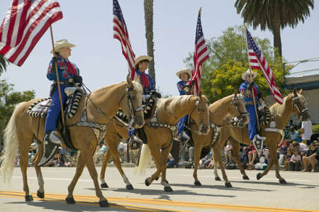 spaniards: Cowboys marching with American Flags displayed during opening day parade down State Street, Santa Barbara, CA, Old Spanish Days Fiesta, August 3-7, 2008 Editorial