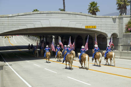 Cowboys marching with American Flags displayed during opening day parade down State Street, Santa Barbara, CA, Old Spanish Days Fiesta, August 3-7, 2009 Editorial