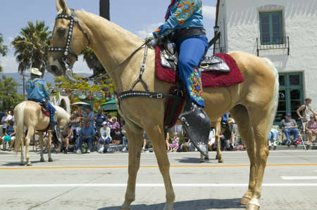 spaniards: Cowgirl on horse during opening day parade down State Street, Santa Barbara, CA, Old Spanish Days Fiesta, August 3-7, 2007 Editorial