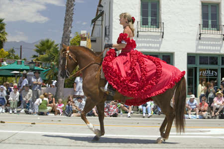 Pretty woman with a red Spanish dress on horseback during opening day parade down State Street, Santa Barbara, CA, Old Spanish Days Fiesta, August 3-7, 2005