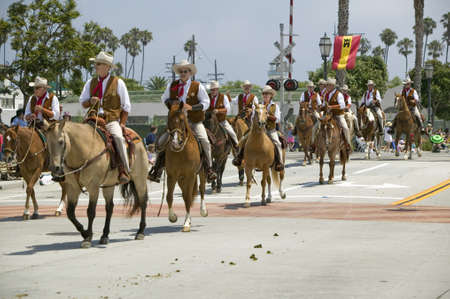spaniards: Cowboys riding down street on horseback during opening day parade down State Street, Santa Barbara, CA, Old Spanish Days Fiesta, August 3-7, 2005
