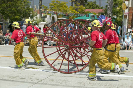 spaniards: Santa Barbara Fire Department pulling old fire engine during opening day parade down State Street, Santa Barbara, CA, Old Spanish Days Fiesta, August 3-7, 2005 Editorial