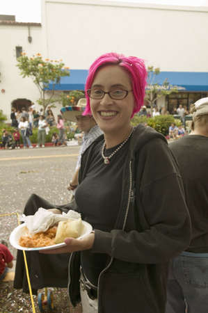 Girl with purple hair eats food at annual Old Spanish Days Fiesta held every August in Santa Barbara, California