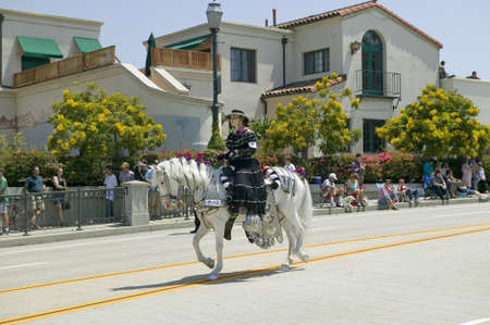 Woman with black Spanish dress riding horse during opening day parade down State Street, Santa Barbara, CA, Old Spanish Days Fiesta, August 3-7, 2005