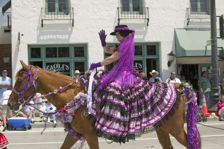 spaniards: Woman with purple Spanish dress riding horse during opening day parade down State Street, Santa Barbara, CA, Old Spanish Days Fiesta, August 3-7, 2005 Editorial