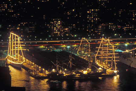 Tall ships docked at night in New York Harbor during the 100 year celebration for the Statue of Liberty, July 3, 1986