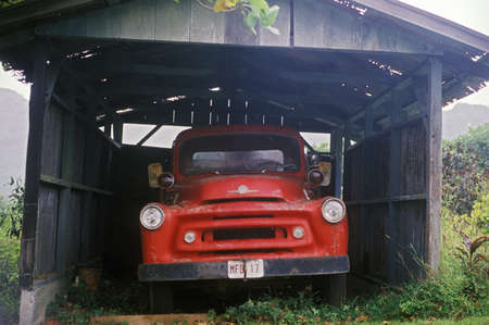 junked: A red truck under an old carport in Hawaii