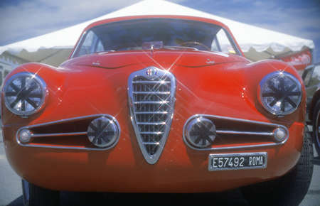An Alfa Romeo Milano red car shown at the 35th Concours D Elegance Show in Pebble Beach, Carmel, CA